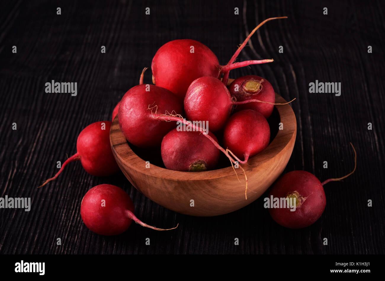 Organici di ravanello rosso sul buio in ciotola di legno sullo sfondo di legno Immagini Stock