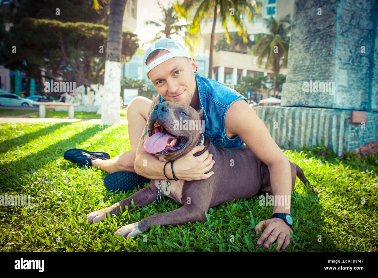 Uomo e cane american pit bull terrier di relax presso il parco abbracciando e abbracciando Foto Stock
