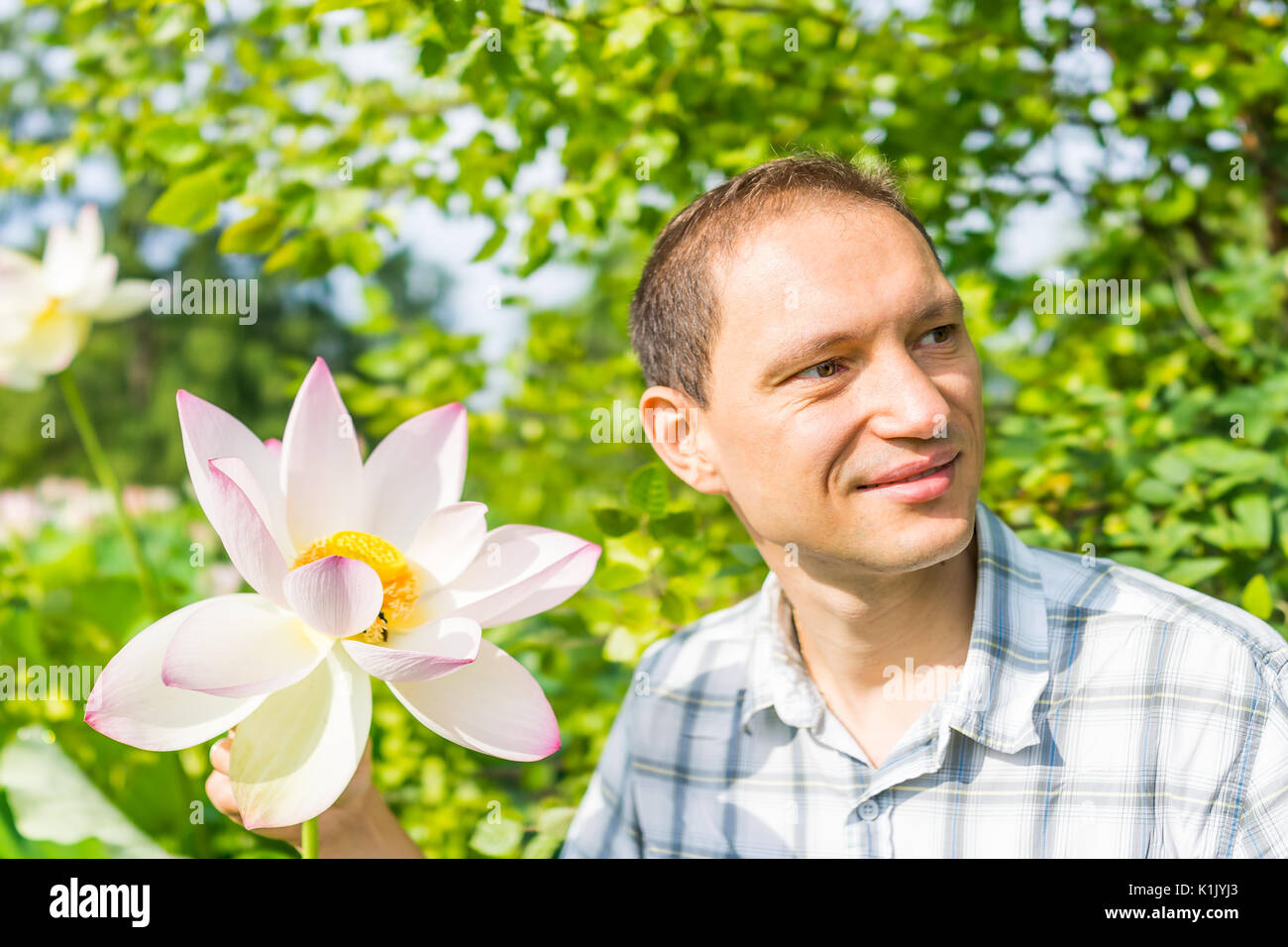 Closeup Ritratto di giovane uomo sorridente holding di un bianco luminoso e rosa fiore di loto con giallo seedpod interno Immagini Stock