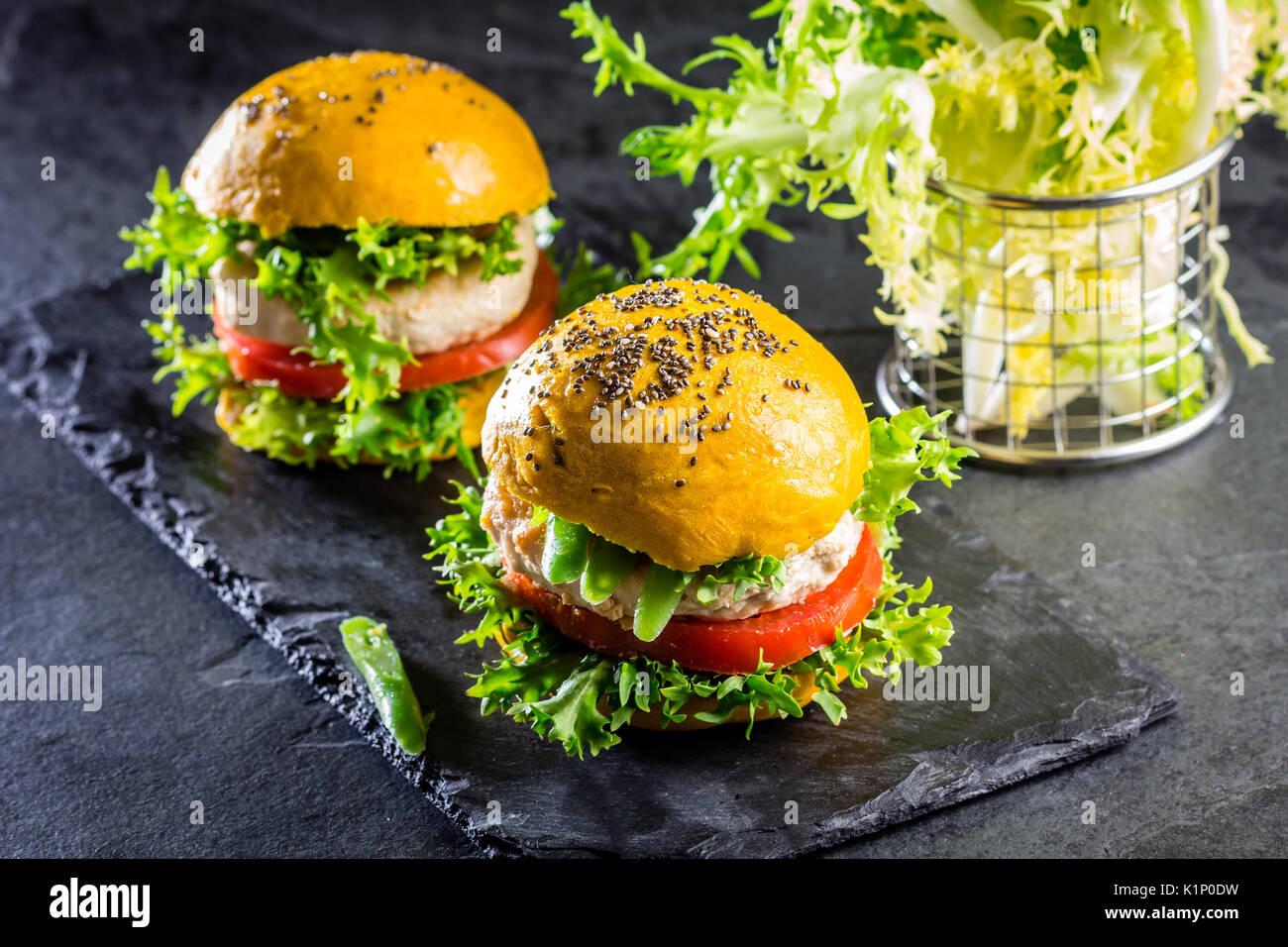 Colorato di giallo hamburger. In casa americana hamburger di pollo hamburger con la curcuma curcuma e chia panini e verdure. Cibo alla moda. Close up, ardesia Immagini Stock