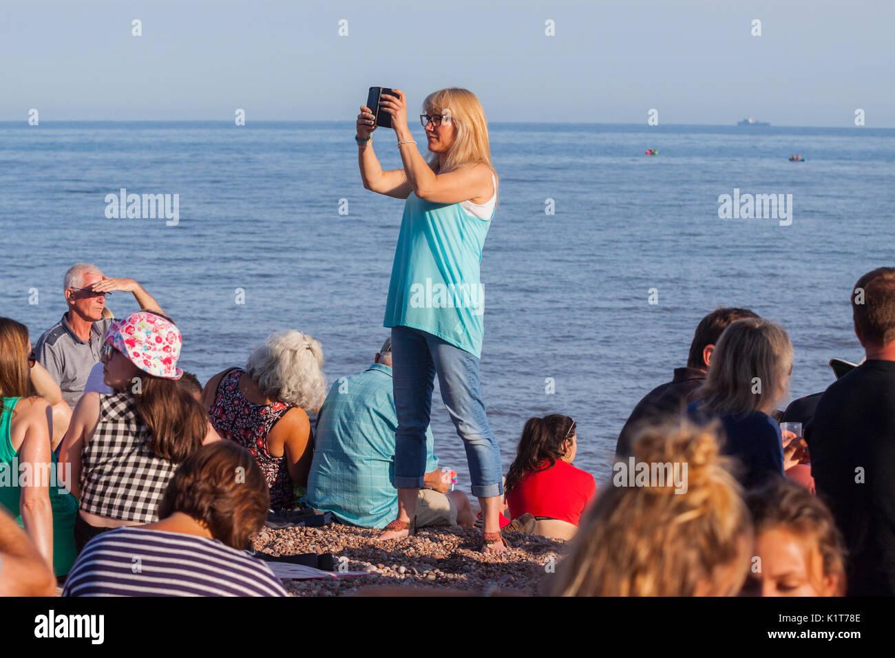 Una giovane donna prende foto video utilizzando un telefono cellulare su una spiaggia. Immagini Stock