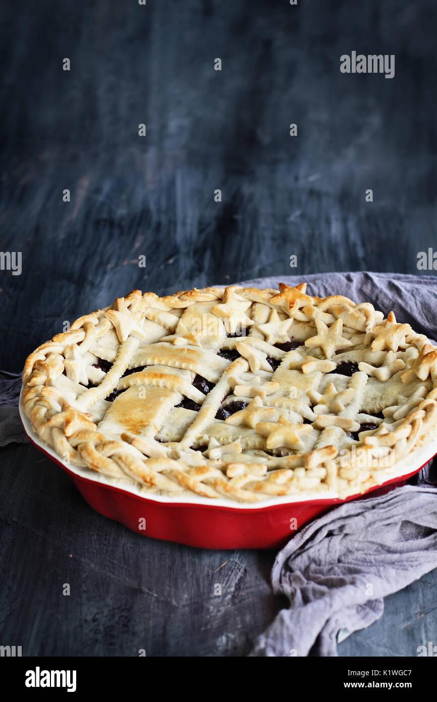 Dolce torta ai mirtilli con reticolo e stelle crosta in un grafico a torta rossa piastra contro un rustico sfondo di legno. Immagini Stock