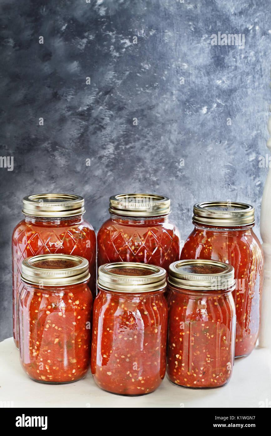 Vasetti di vetro conserve con salsa fatta in casa seduti su un vecchio paese bianco poltrona di fronte a uno sfondo Foto Stock