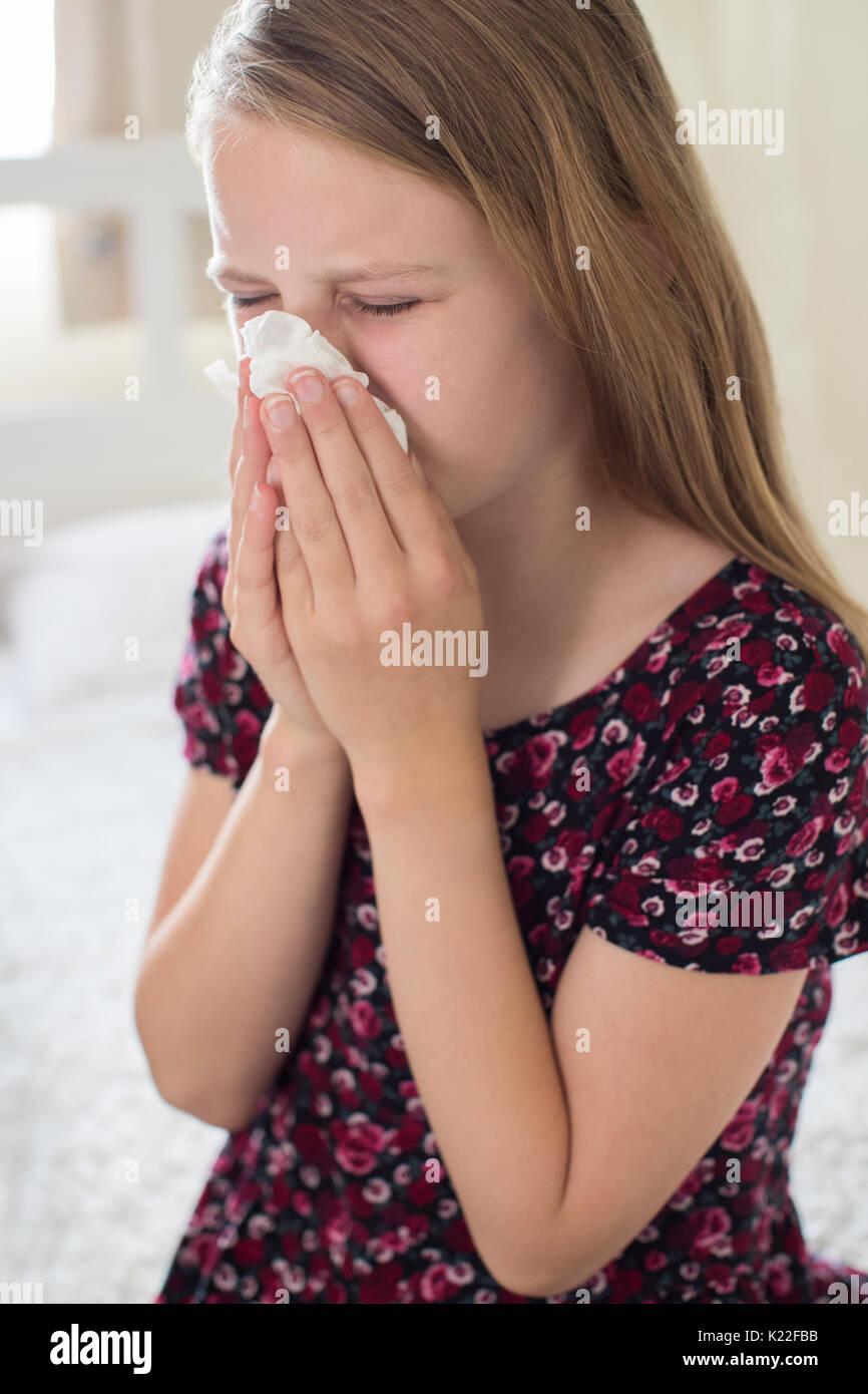 Ragazza sofferenza con il freddo starnuti nel tessuto Immagini Stock
