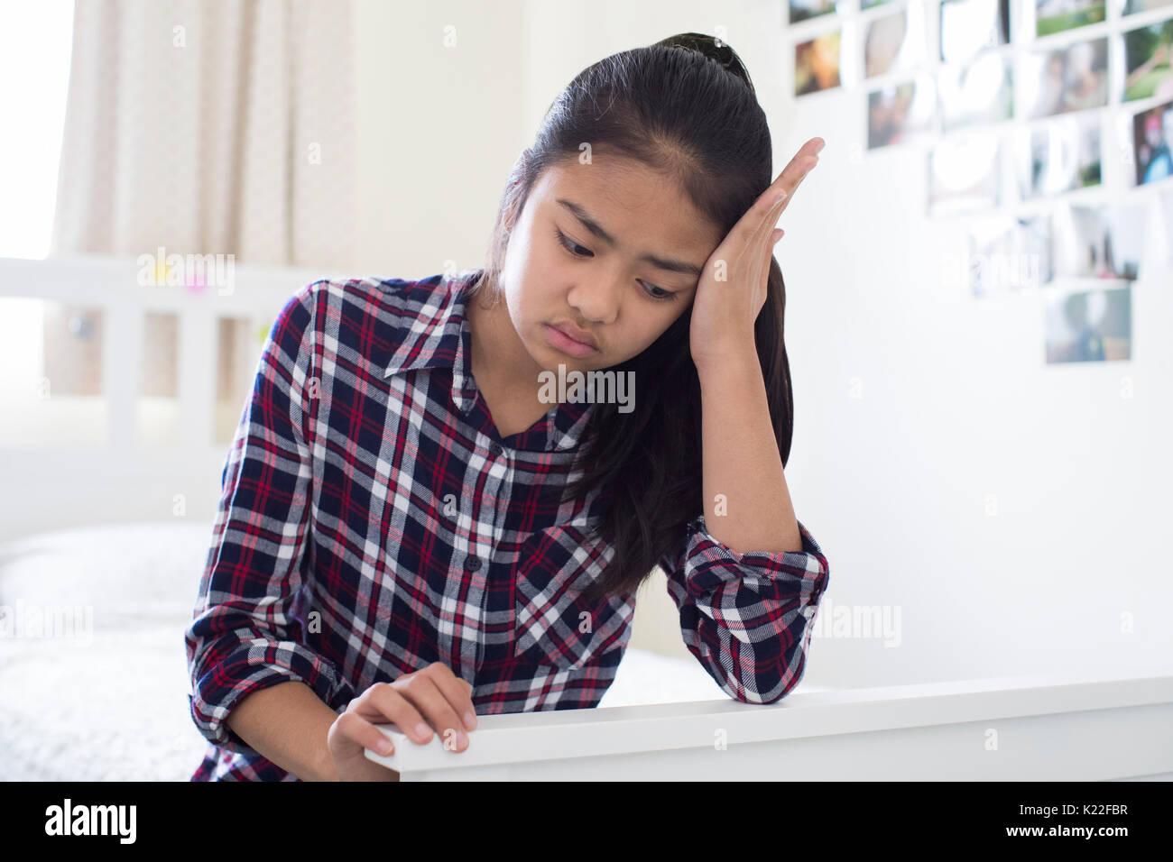 Sottolineato giovane ragazza seduta in camera da letto a casa Immagini Stock