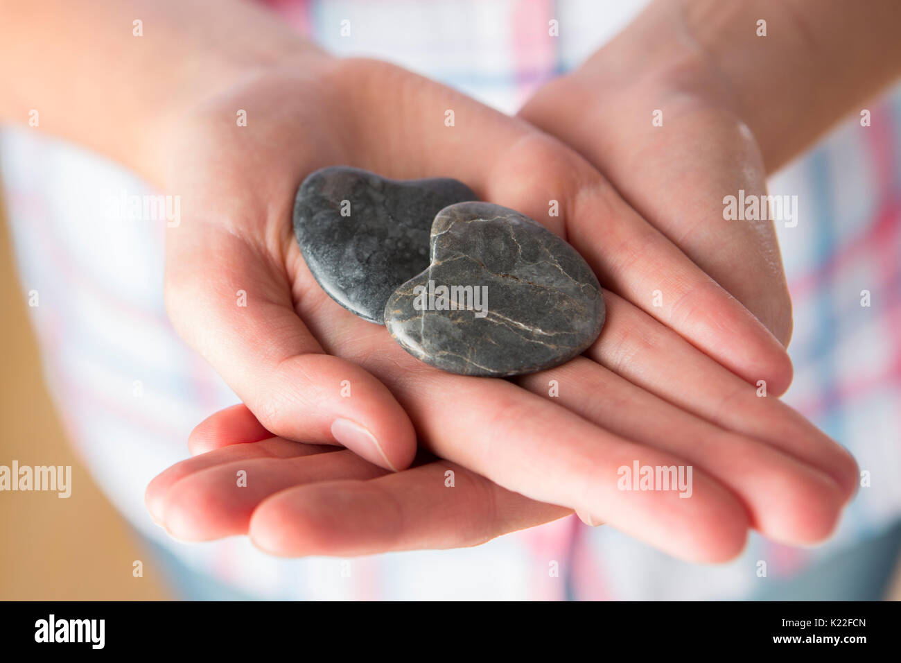 Stretta di mano che regge due cuore pietre sagomate Immagini Stock