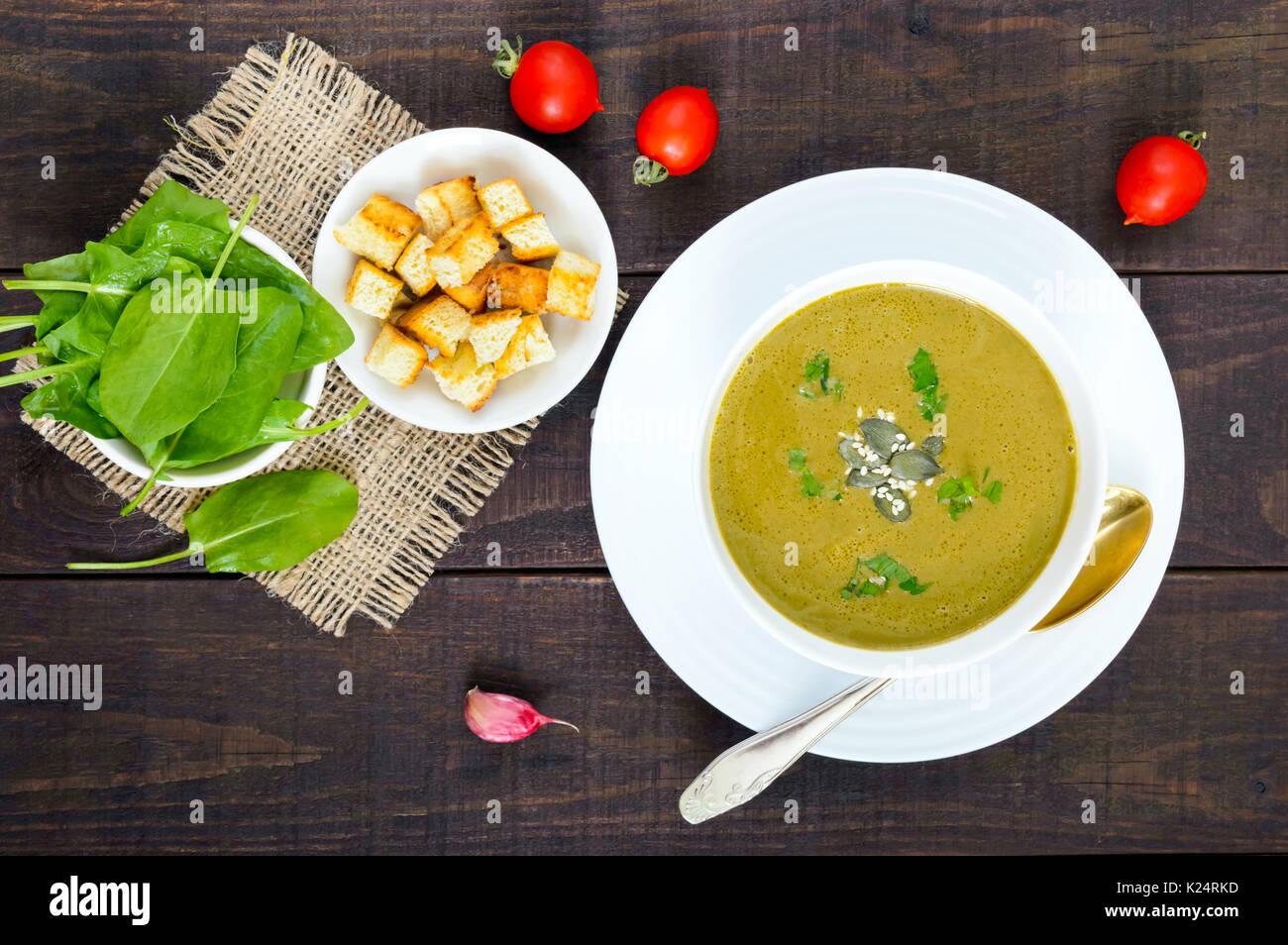 Crema di verdure minestra con spinaci e patate in una ciotola bianco con aglio crostini su legno scuro dello sfondo. Foto Stock