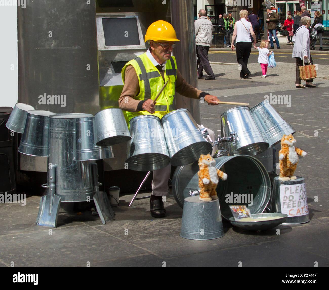 Busker, Techno scomparto stagno uomo, INDOSSARE ELMETTO & alta visibilità giacca e la riproduzione di musica sui bidoni di metallo nella città di Glasgow, Scozia Immagini Stock
