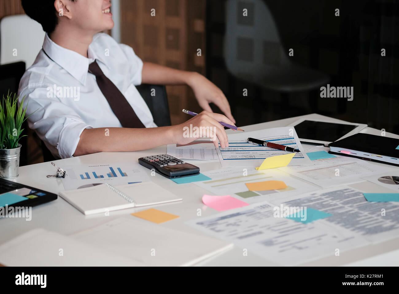 Giovane Imprenditore asiatico seduto in ufficio e sorriso in faccia, il fuoco selettivo. Immagini Stock