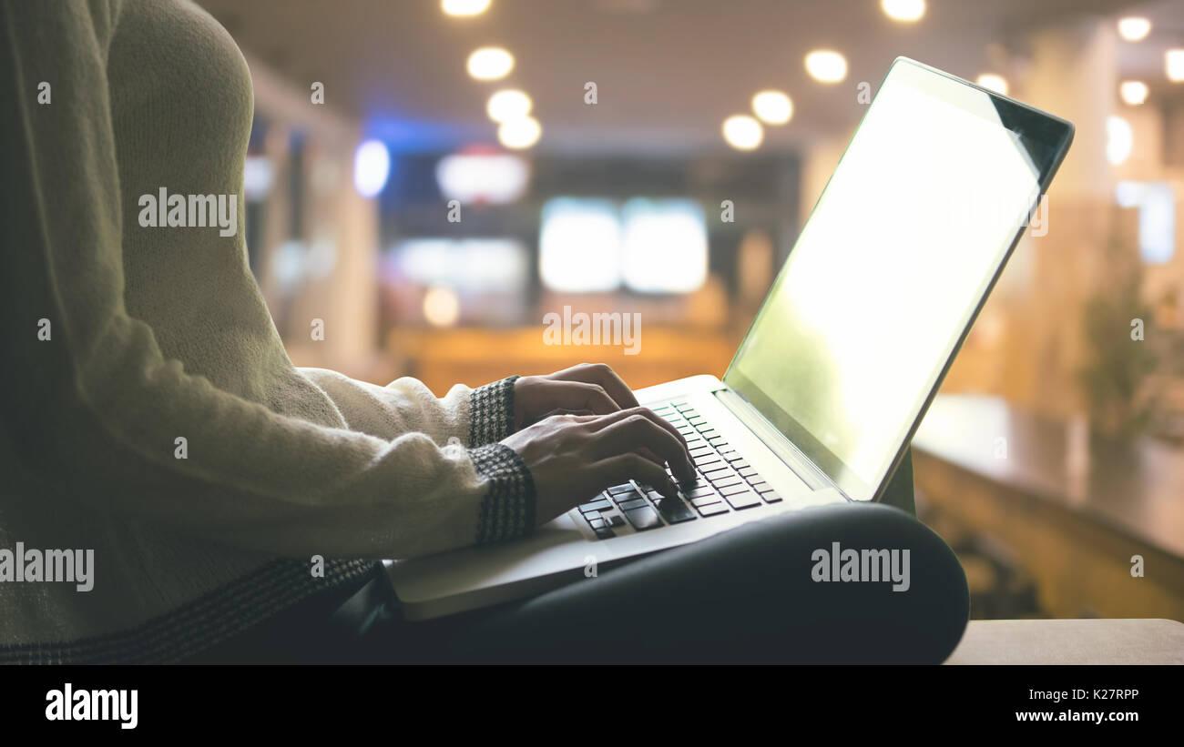 Donna che utilizza computer portatile in ufficio a casa di notte tempo. Immagini Stock