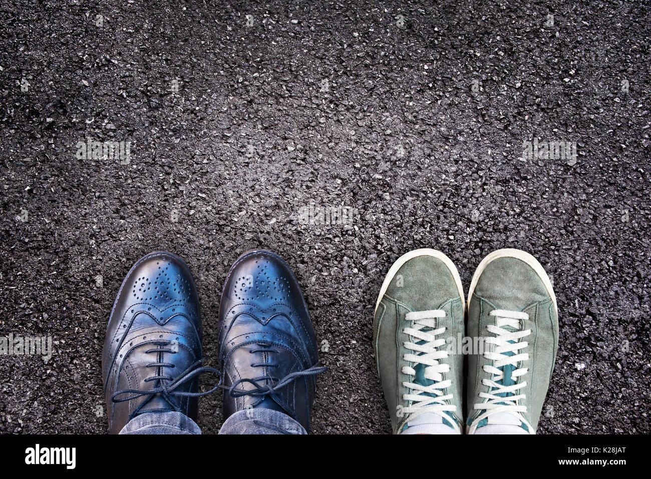 Sneakers e scarpe business fianco a fianco su asfalto, equilibrio tra lavoro e vita familiare nozione Foto Stock