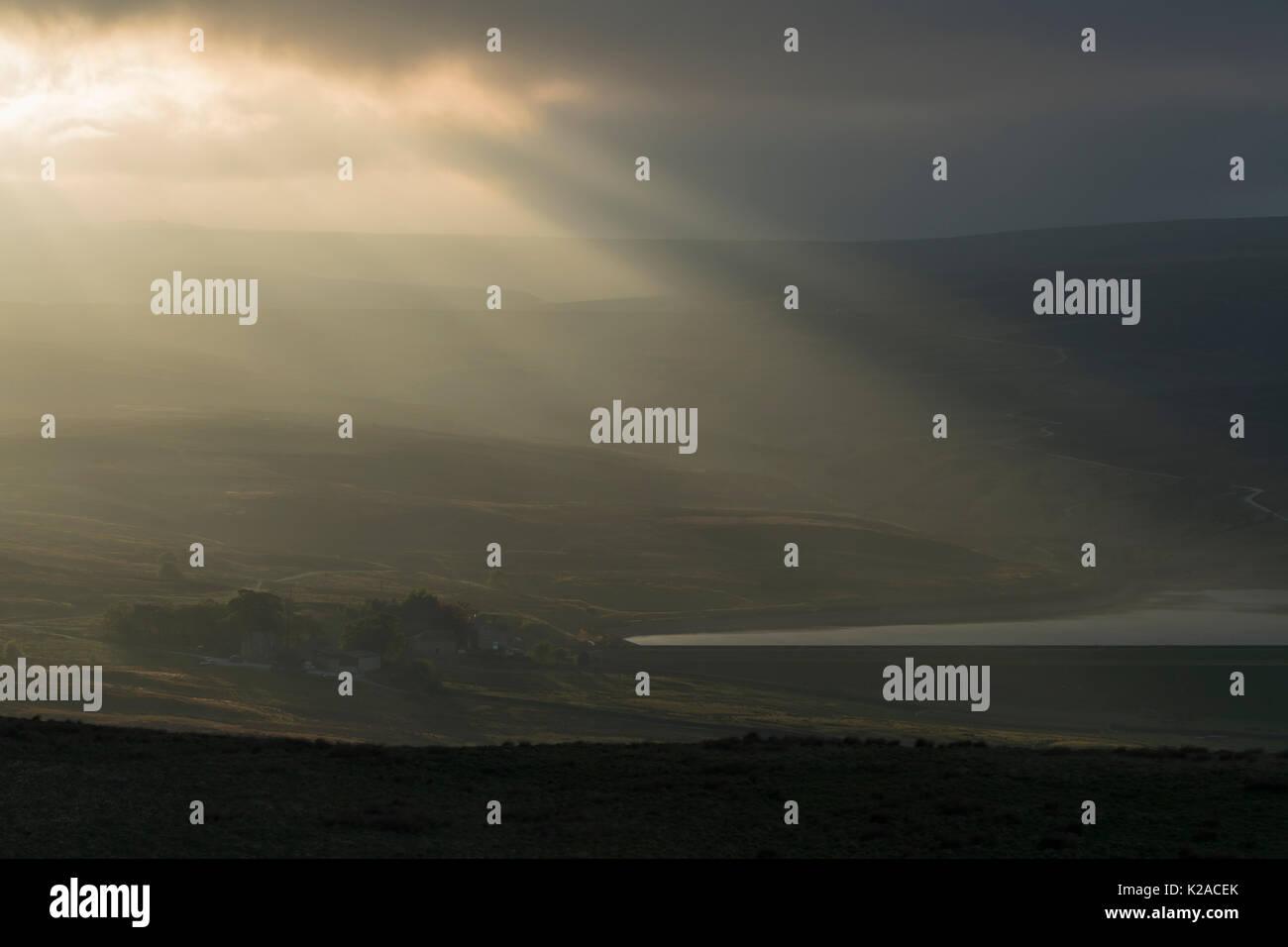 Raggi di luce del sole serale flusso verso il basso fuori di nuvole scure su inferiore serbatoio Barden & scenic campagna di laminazione - Wharfedale, nello Yorkshire, Inghilterra, Regno Unito. Immagini Stock