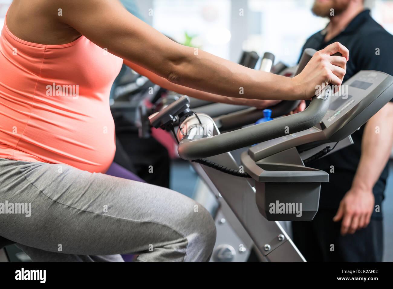 Donna incinta la filatura sul fitness bike in palestra Immagini Stock