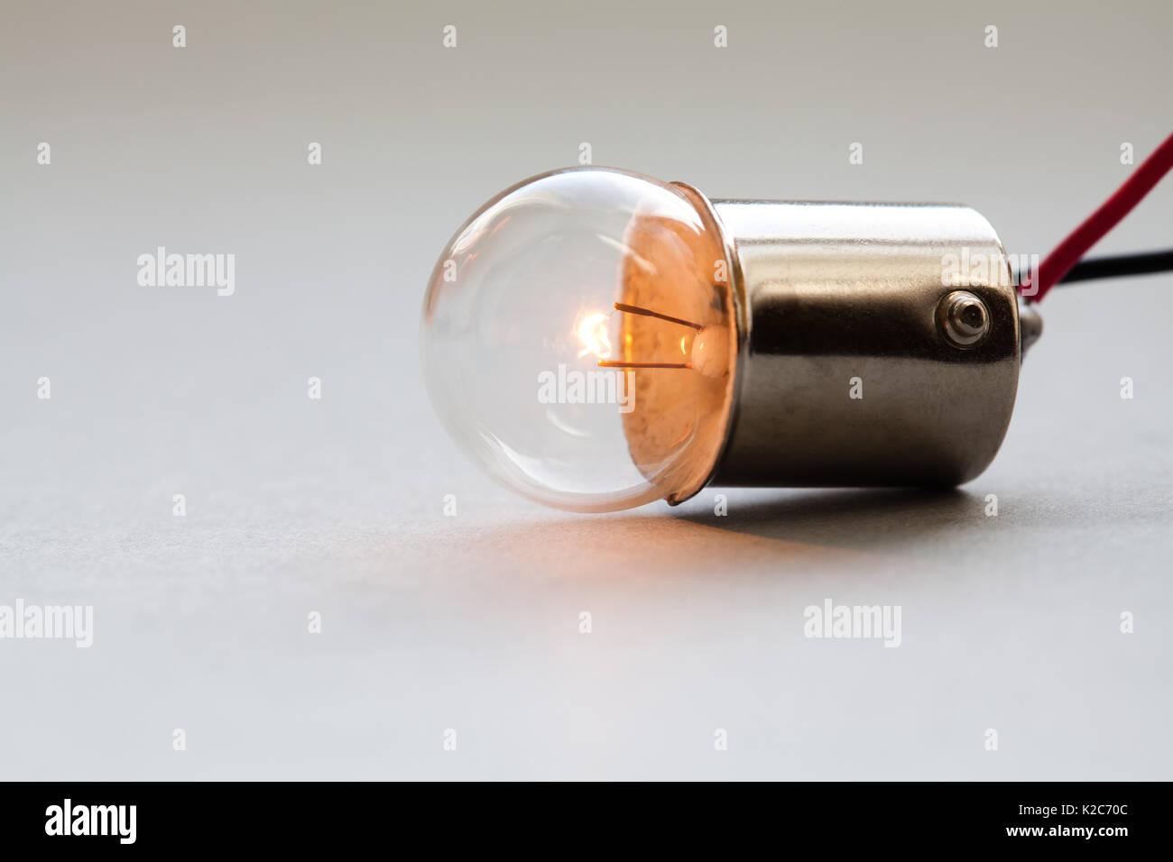 Lampadina elettrica con il filo elettrico posa su uno sfondo grigio. Superficie sferica ideale. Incandescente lampadina a filamento di close-up. Soft focus, spazio di copia Immagini Stock