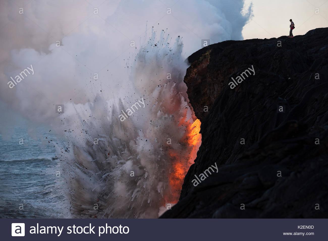 Un escursionista non autorizzate in una zona soggetta a restrizioni di avventurarsi fuori su un instabile scogliera sul mare su di un tubo di lava dove hot lava dal 61G flusso dal vulcano Kilauea entra nell'oceano dalla estremità aperta di un tubo di lava, proprio come una violenta esplosione di vapore genera hot rocce di pomice a ritornare sulla scogliera sul mare, in corrispondenza della voce Kamokuna nel Parco Nazionale dei Vulcani delle Hawaii, Puna, Hawaii. Gennaio 2017. Immagini Stock