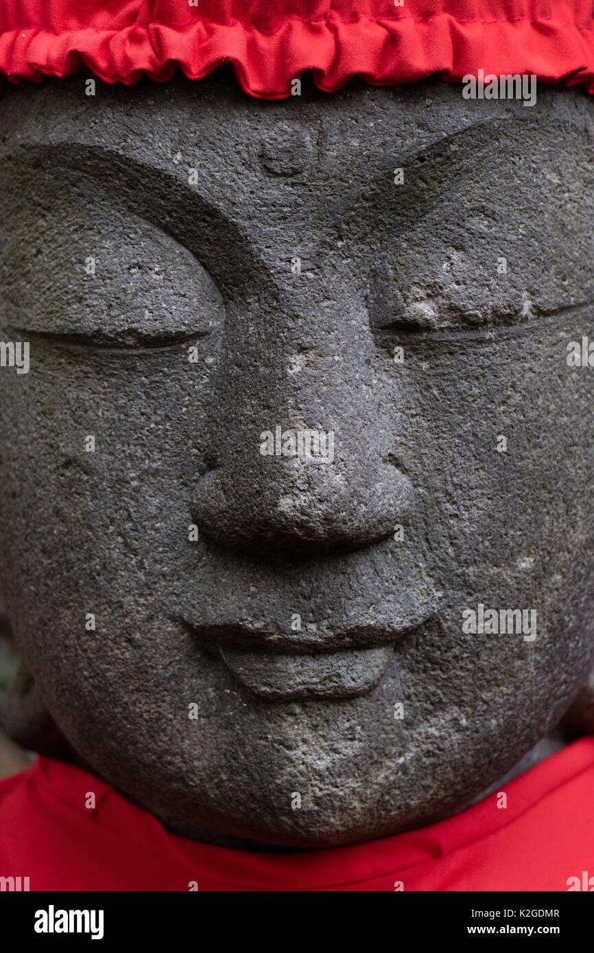 Tokyo, Giappone, buddista statua di pietra di fronte indossando un Red Hat Immagini Stock