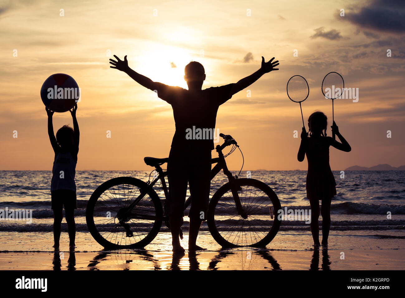 Padre e figli giocando sulla spiaggia al tramonto. Concetto di felice famiglia amichevole. Immagini Stock
