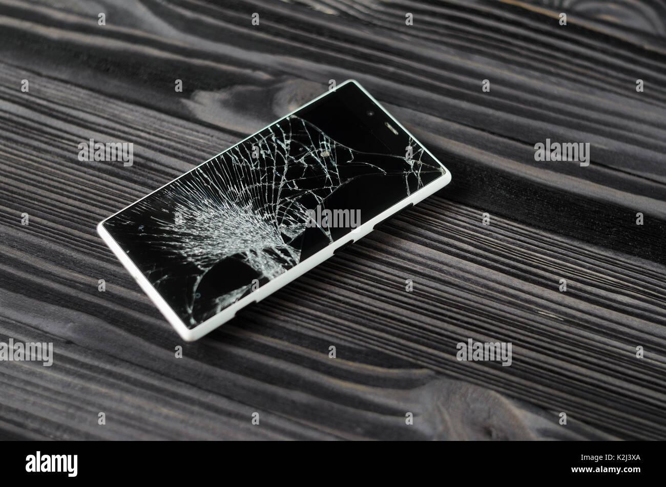 Smartphone Con Schermo Rotto Su Scuro Dello Sfondo In Legno Foto