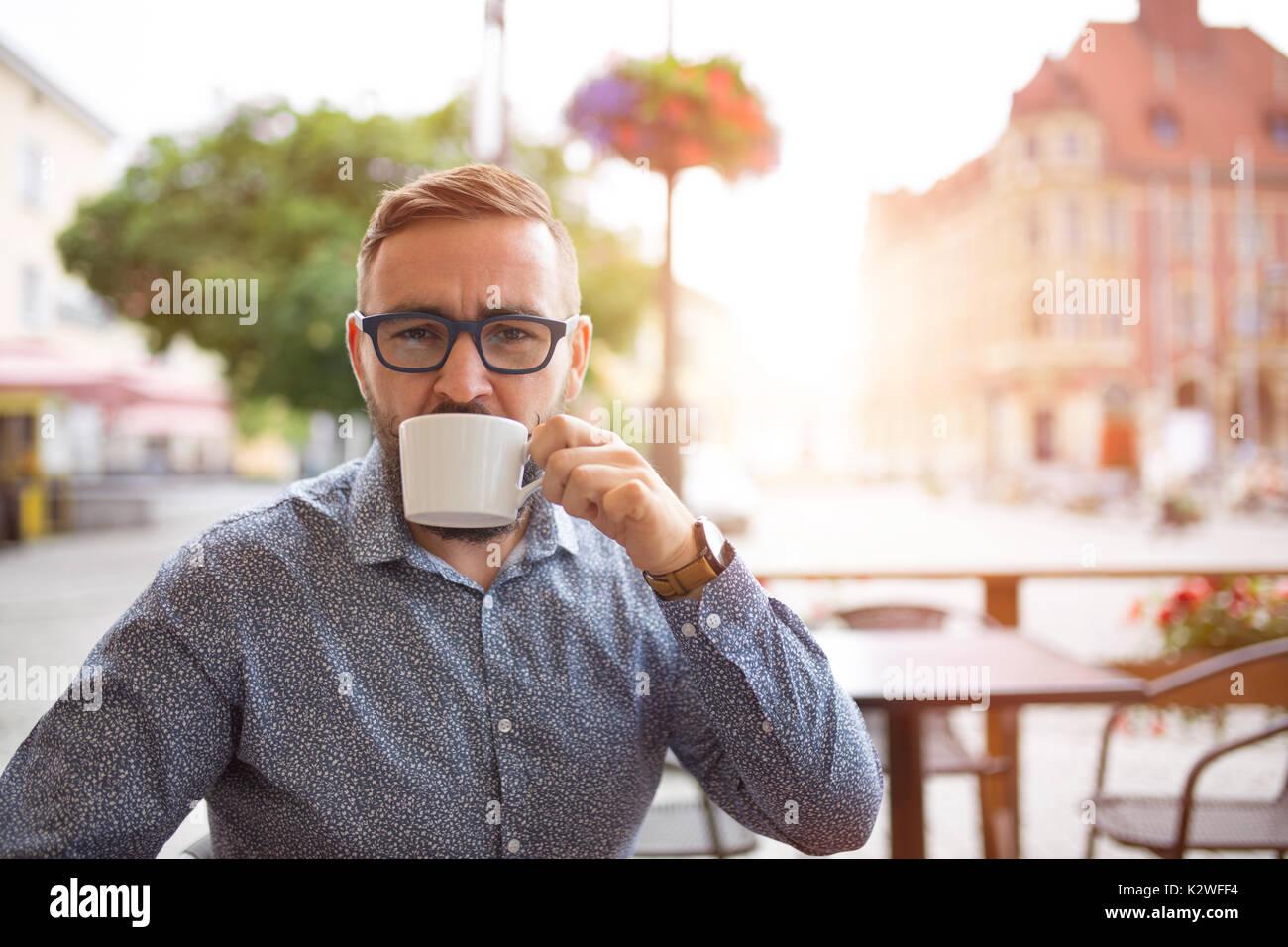Uomo elegante bere cappuccino in cafe-giardino alla città vecchia Immagini Stock