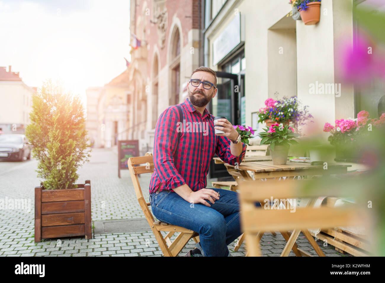 Uomo seduto nella caffetteria giardino e bere il caffè da asporto Immagini Stock