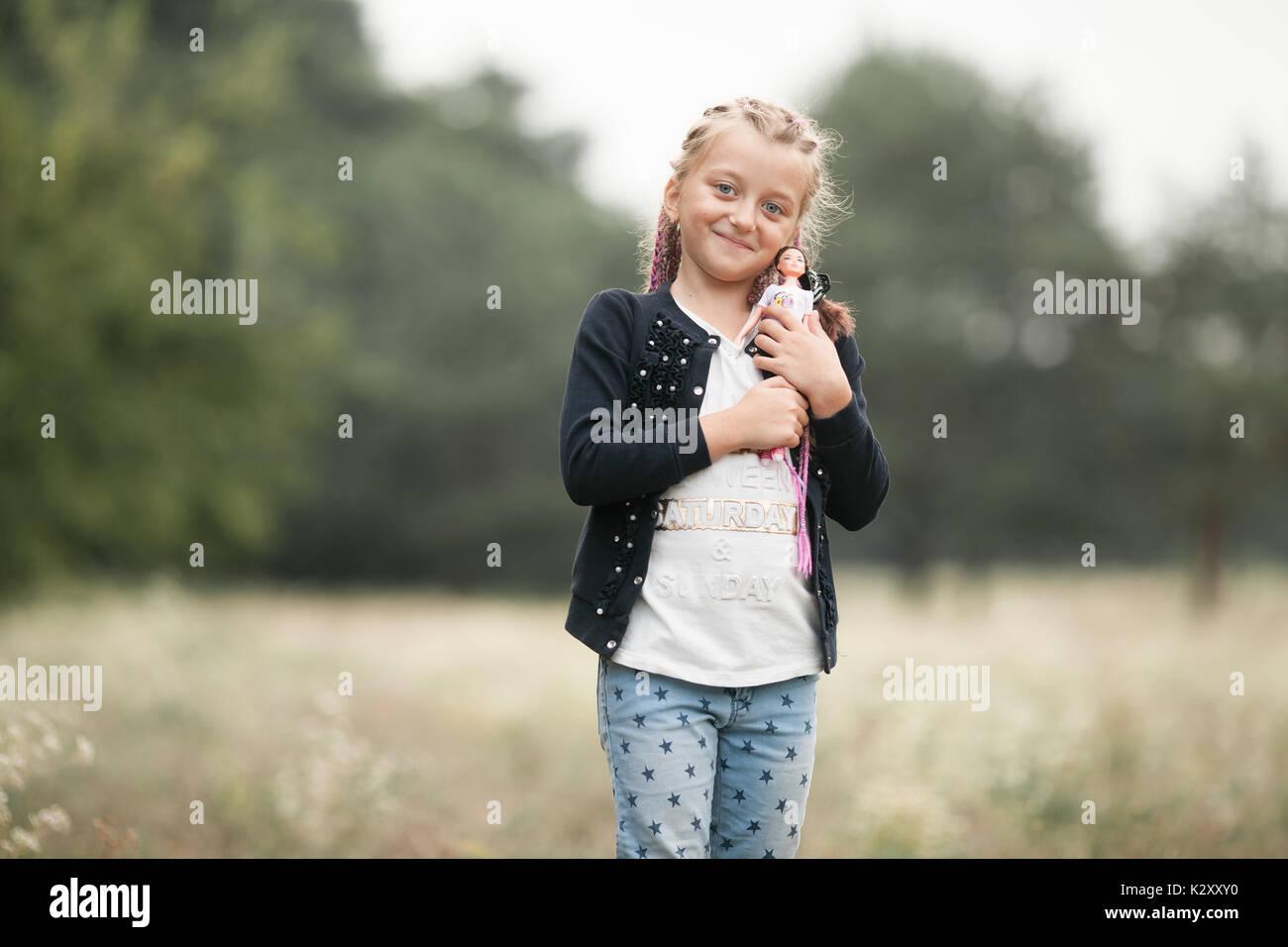 Bambino ragazza con pig-tail sorrisi e gioca con la sua bambola a piedi. Immagini Stock