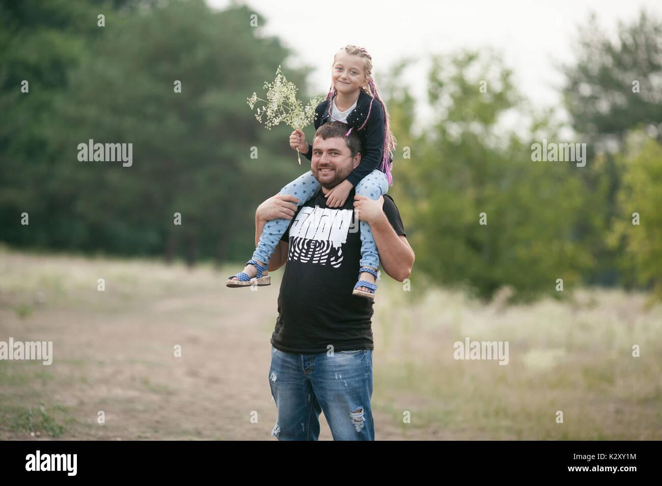 Padre Felice con la figlia sorriso sulla passeggiata nel parco. Papà mettere bambino ragazza sulle sue spalle. Immagini Stock