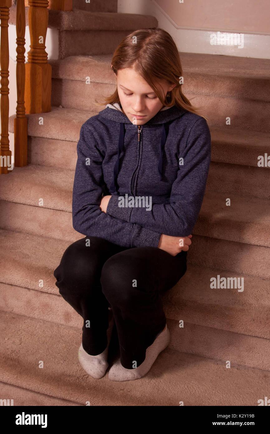 Ragazza seduta sulle scale tappezzate, con le braccia incrociate, abbattuto gli occhi e labbra busbana francese. Immagini Stock