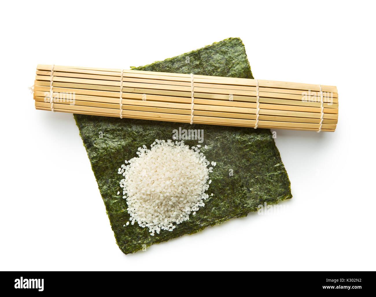 Green nori foglio , riso e tappetino di bambù isolati su sfondo bianco. Sushi ingredienti. Immagini Stock