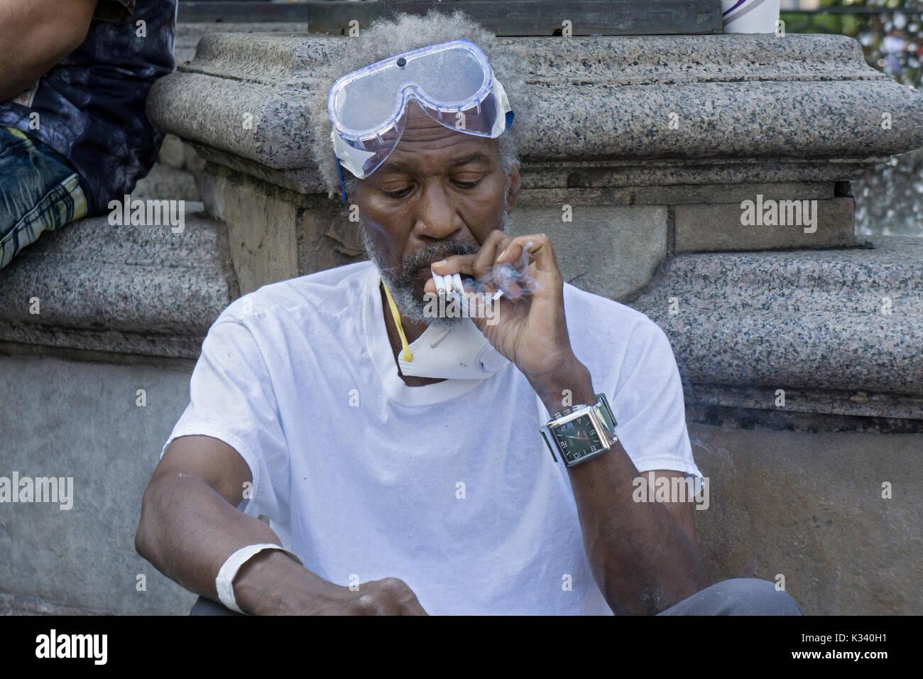Un uomo di fumare tre sigarette in un momento indossando occhiali  protettivi e una maschera facciale f9bbda0bcd4b