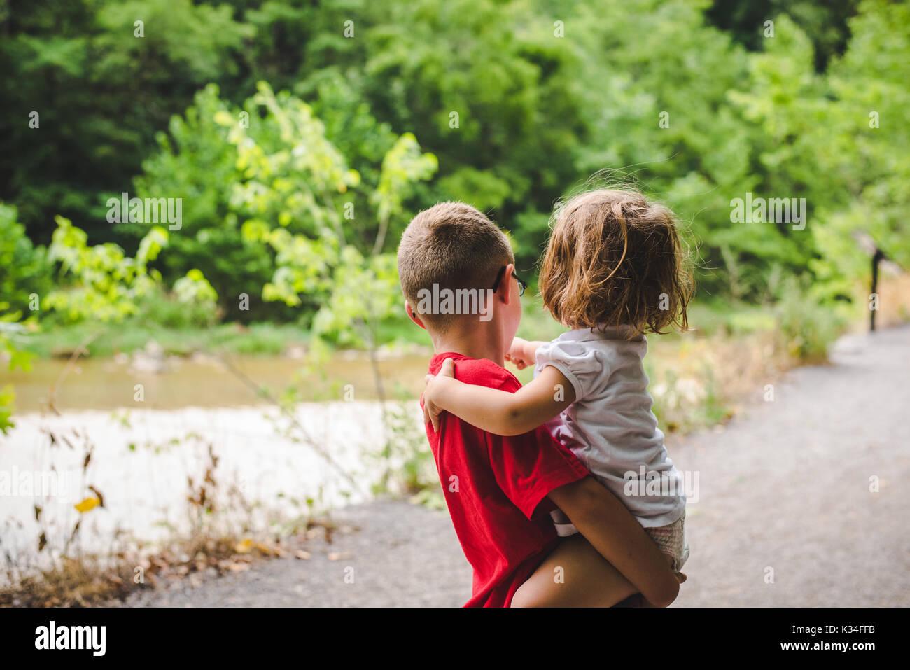 Un ragazzino che tiene una bambina su una strada fiancheggiata da alberi. Immagini Stock