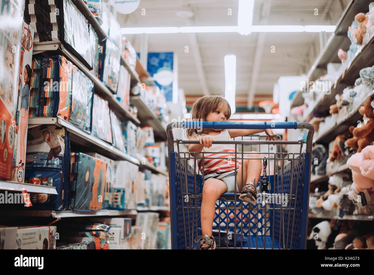 Un bambino si siede in un carrello di shopping in un negozio di giocattoli. Foto Stock