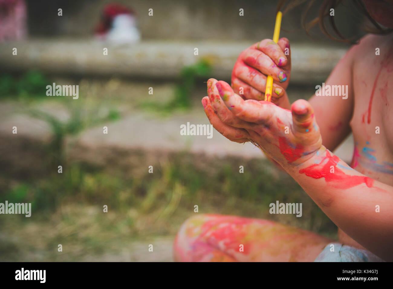 Un bambino dipinge sulla sua mano. Immagini Stock