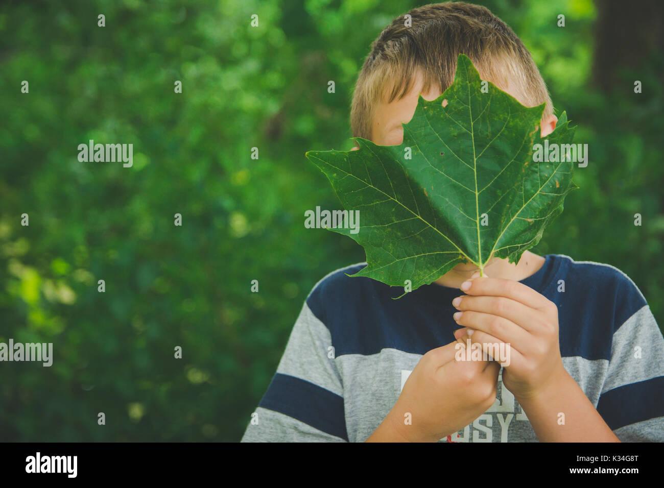 Un giovane ragazzo detiene una foglia verde nella parte anteriore del suo volto. Foto Stock