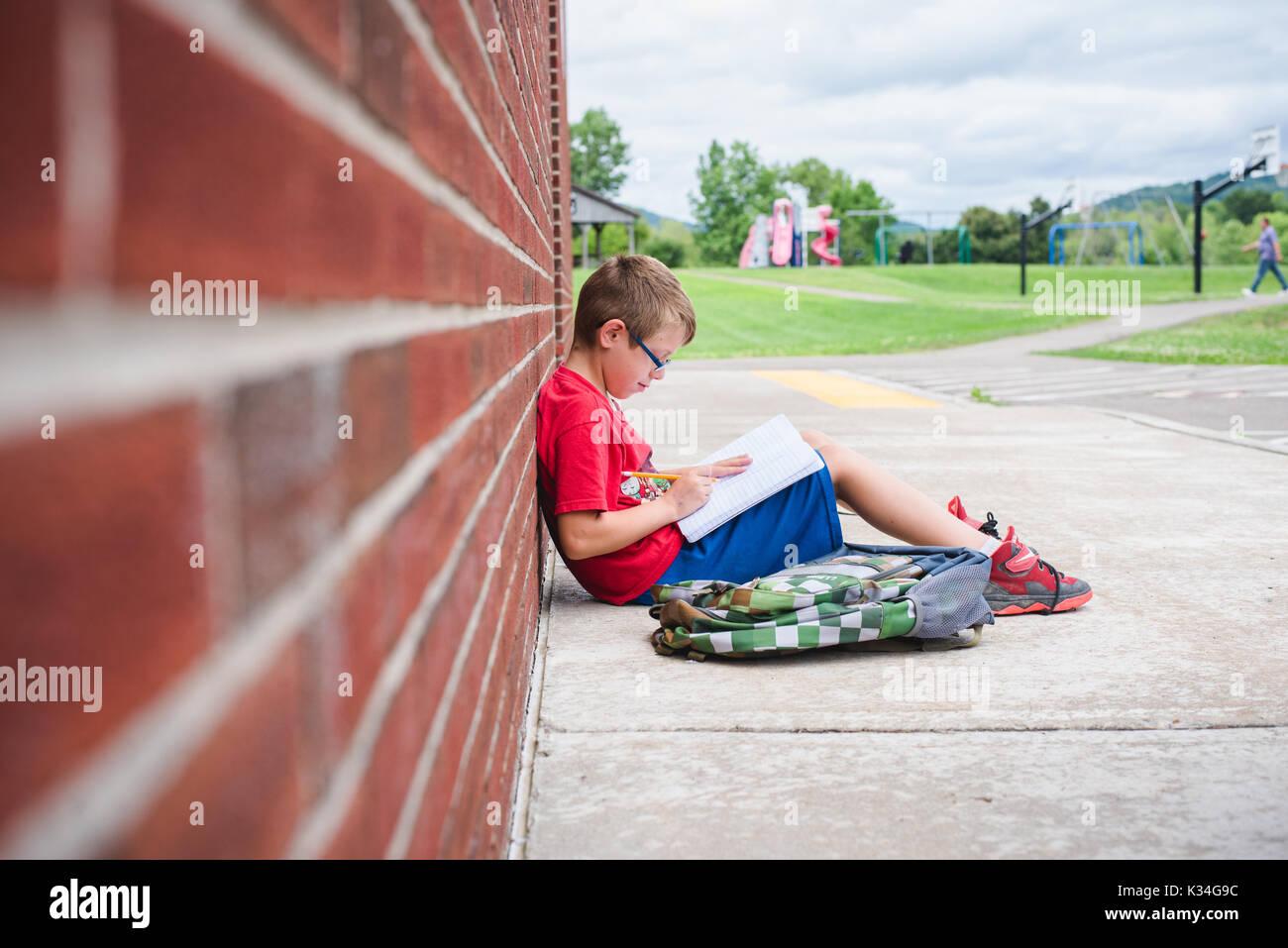 Un ragazzo studi un libro mentre appoggiata contro un muro di mattoni di una scuola Immagini Stock