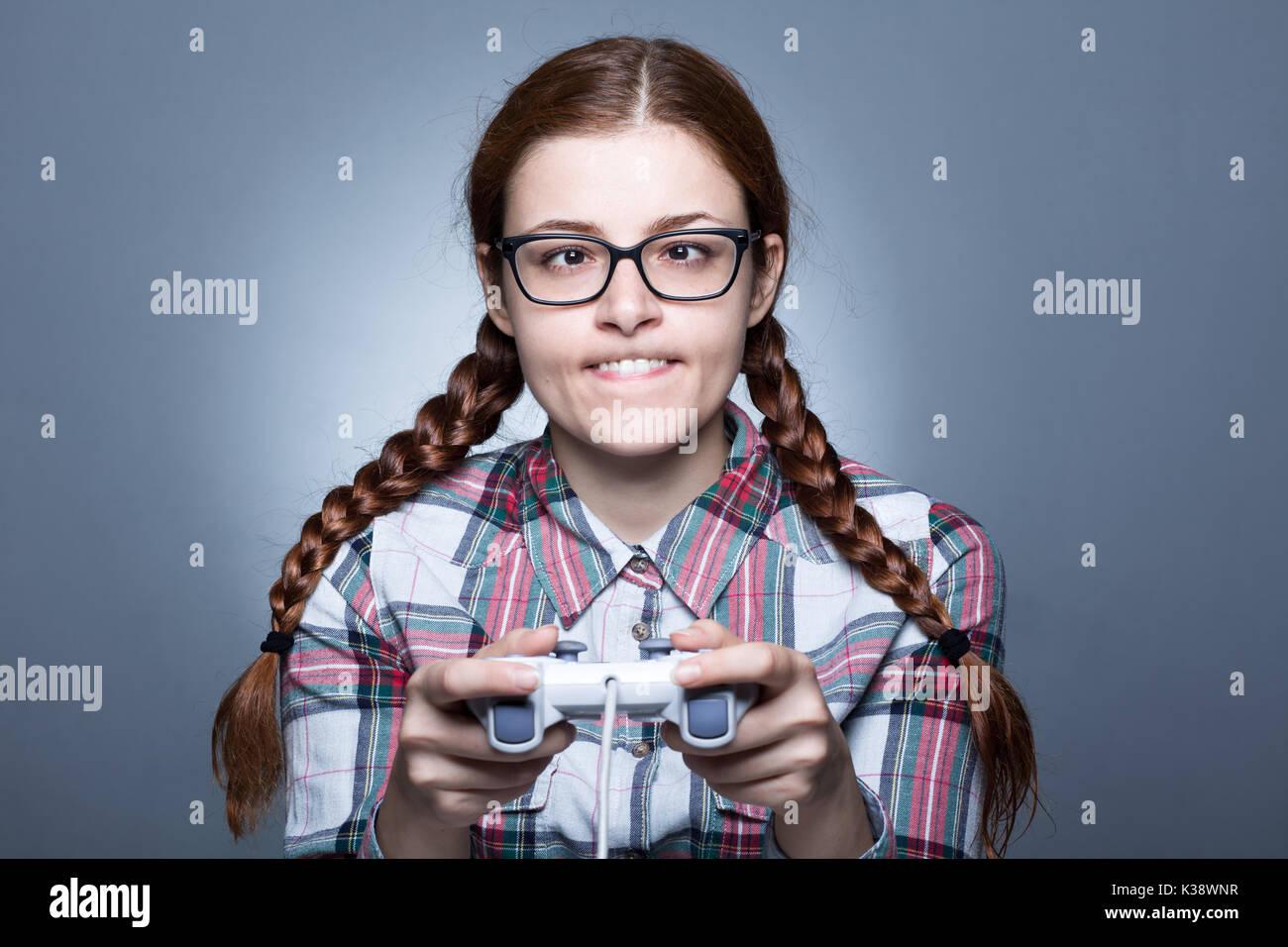 Nerd donna con treccia giocare ai videogiochi con un joypad Immagini Stock