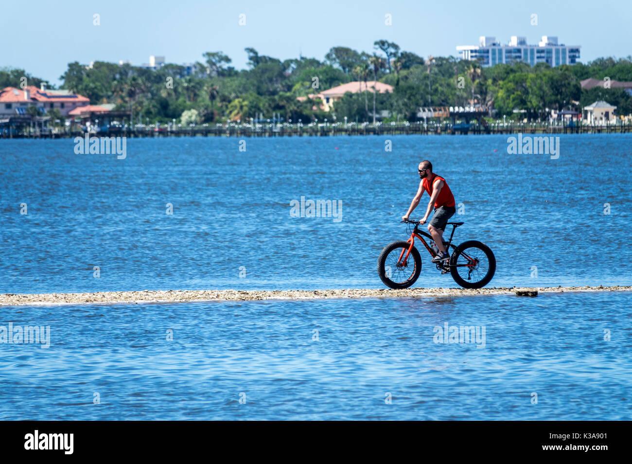 Florida Ormond Beach Halifax molo sul Fiume alta marea bicicletta Ciclismo uomo acqua beach pneumatici Immagini Stock