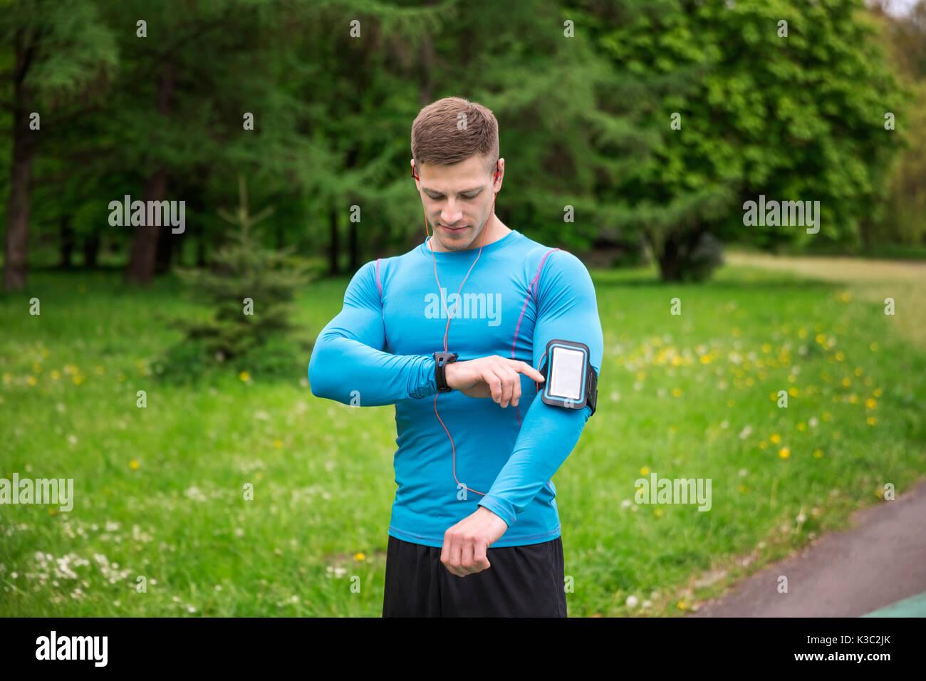 Una foto di giovani, ben costruito uomo controllando il suo tempo durante il jogging. Immagini Stock
