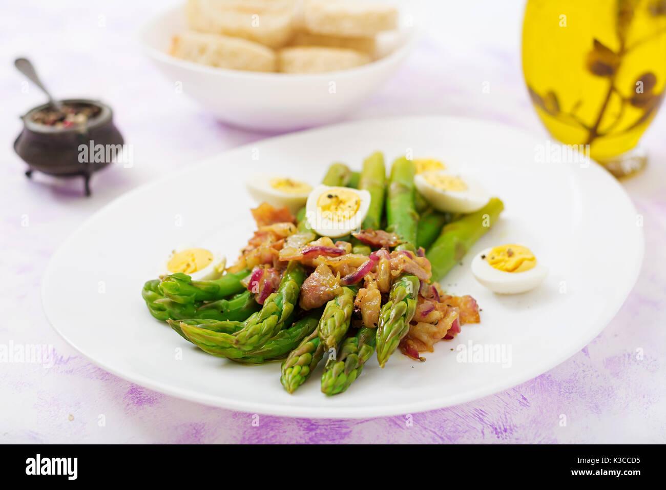 Giovani germogli di asparagi con prosciutto e uova di quaglia Immagini Stock