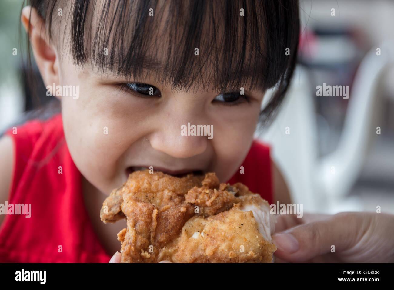 Asian madre cinese e la figlia di mangiare pollo fritto al ristorante al coperto Immagini Stock