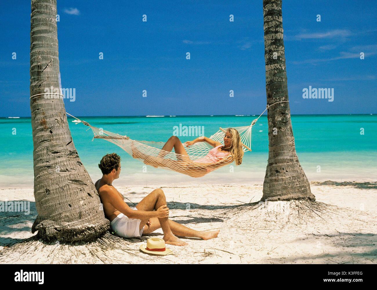 Le coppie in spiaggia con amaca Immagini Stock