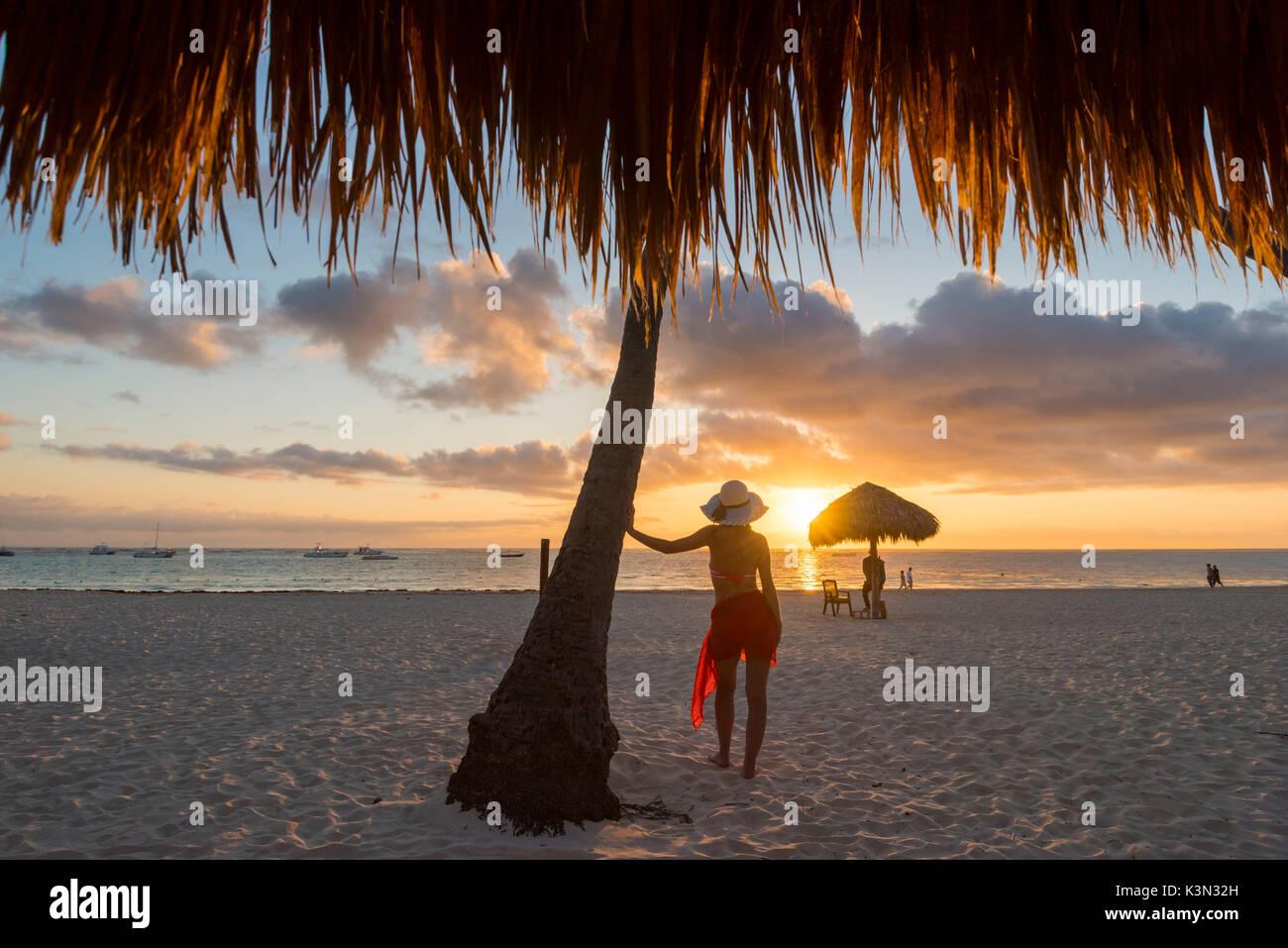 Bavaro Beach, Bavaro, Higuey, Punta Cana, Repubblica Dominicana. La donna da ombrelloni di paglia sulla spiaggia al tramonto (MR). Immagini Stock