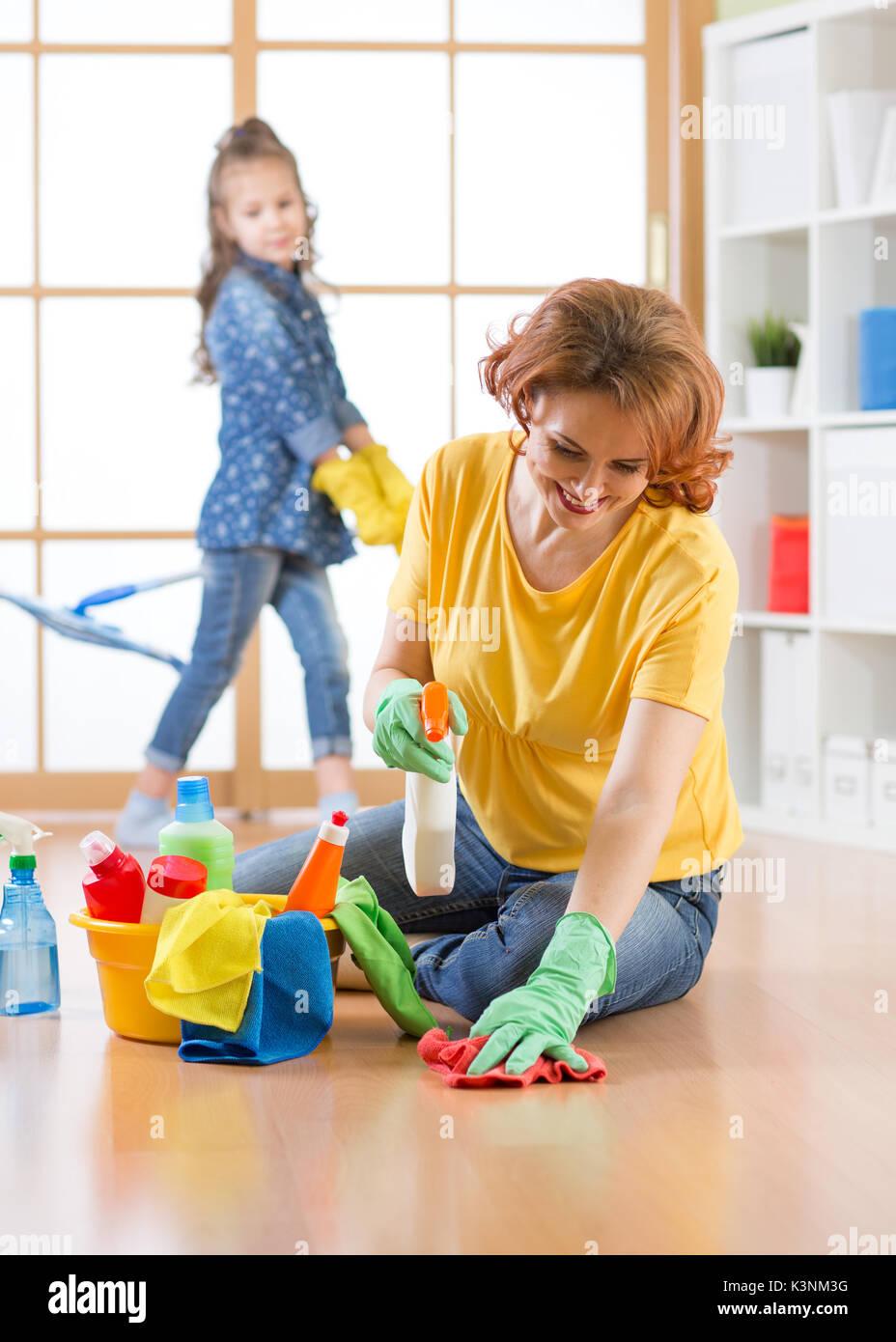 La famiglia felice pulisce la camera. Madre e figlia fare pulizia in casa. Immagini Stock