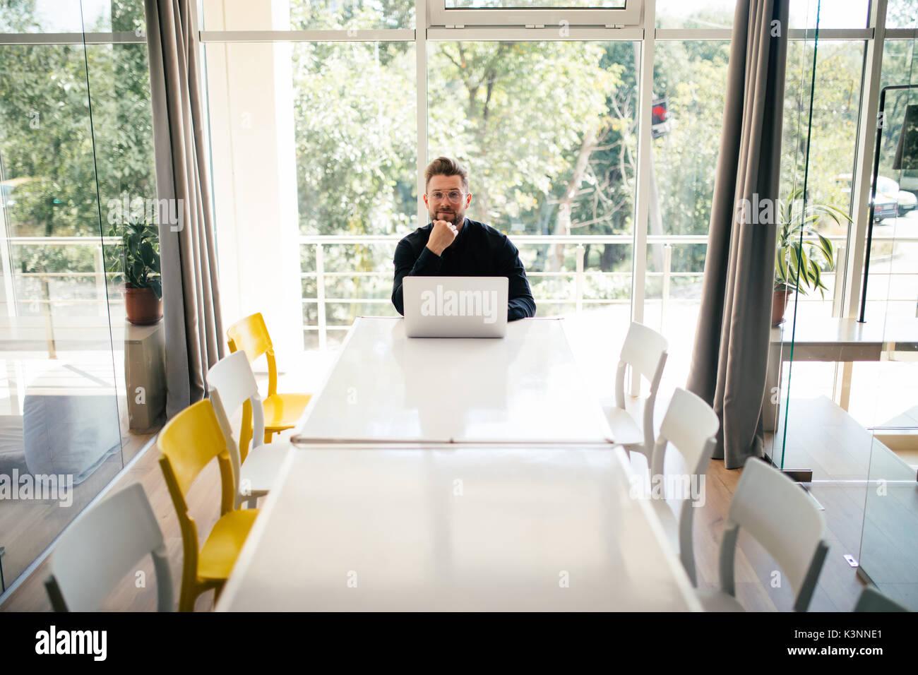 Bel giovane uomo d affari con computer portatile da solo nella grande e luminosa sala conferenze Immagini Stock