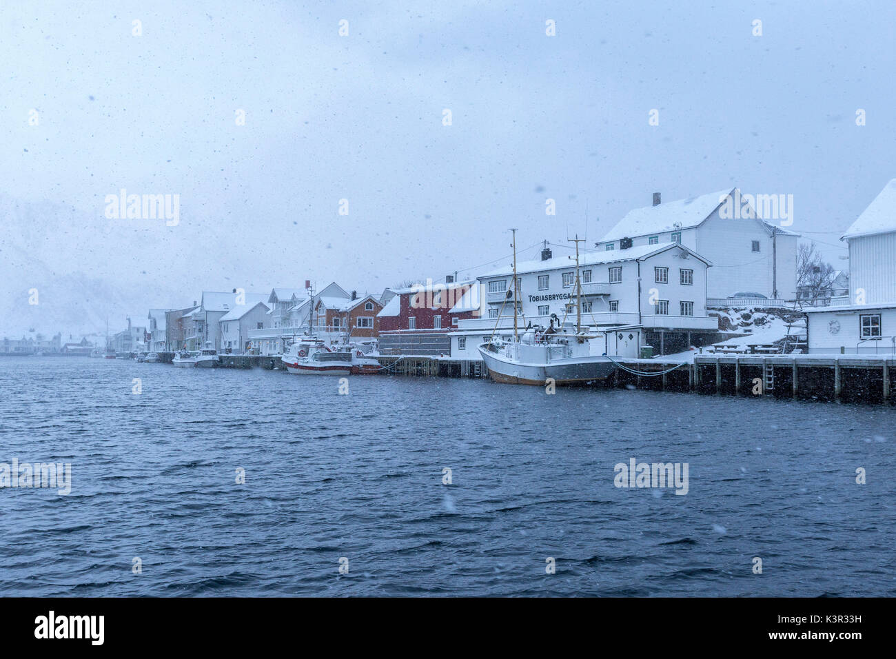 La nevicata oltre il tipico villaggio di pescatori di Henningsvaer Isole Lofoten Norvegia del Nord Europa Immagini Stock