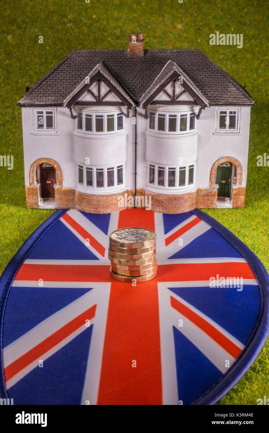 Modello di casa, Sterling Pound monete (con nuovo £ 1 moneta) e Union Jack, per raffigurare costa come un regno unito aumento dei tassi, home comprare, affittare, spostamento, ecc. Immagini Stock
