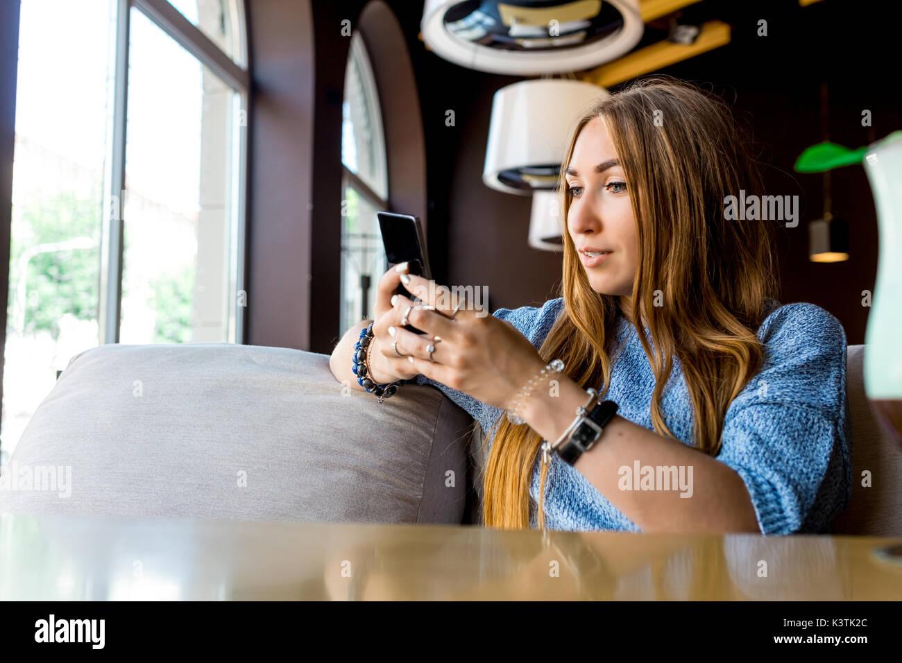 Portret del giovane femmina la lettura di sms sul cellulare in cafe. Tonica. Messa a fuoco selettiva. Immagini Stock