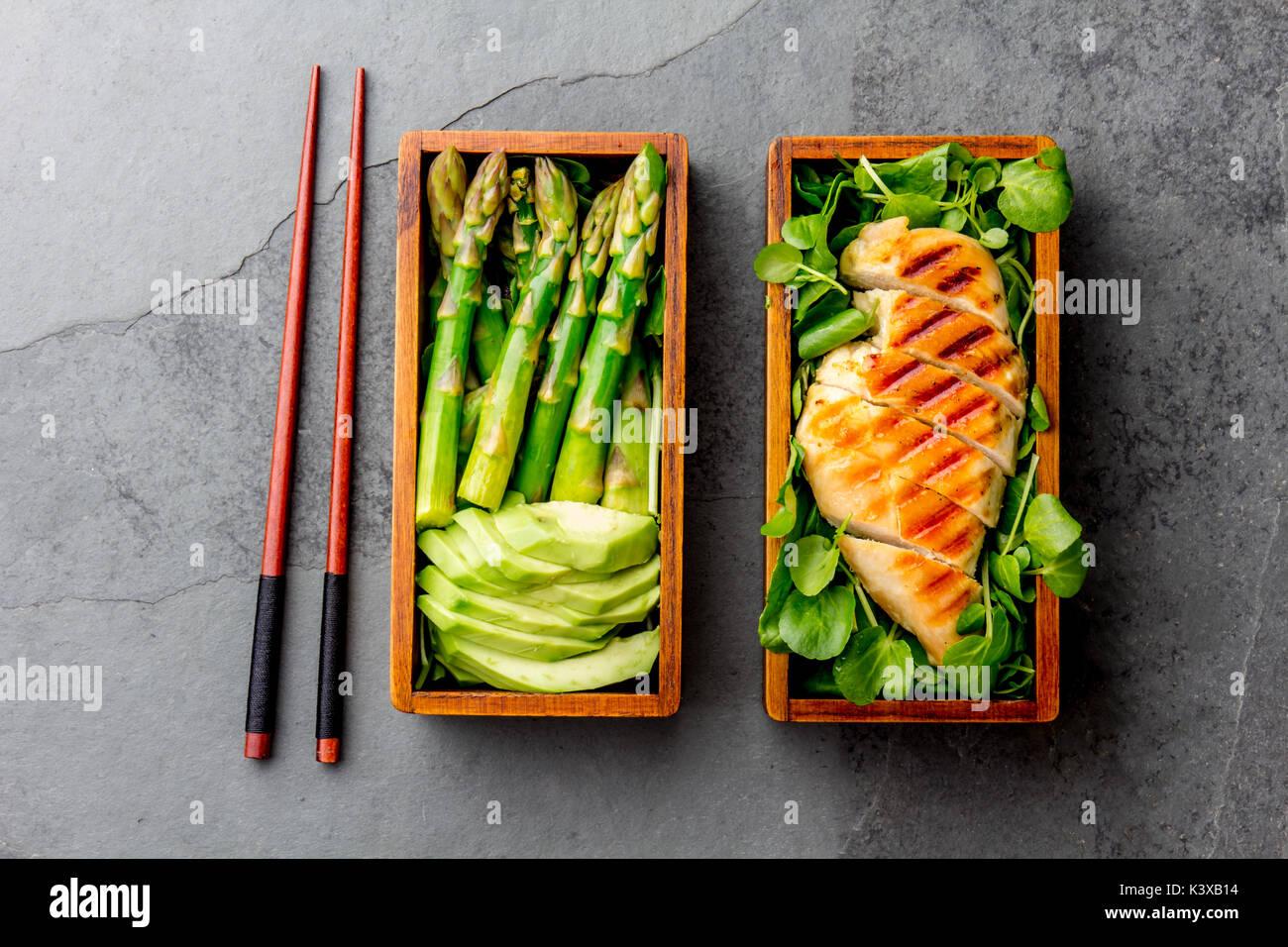 Un sano pranzo in giapponese in legno scatola di Bento. Equilibrato il cibo sano chucken grigliate e avocado con asparagi e insalata verde. Vista superiore, grigio ardesia bac Immagini Stock