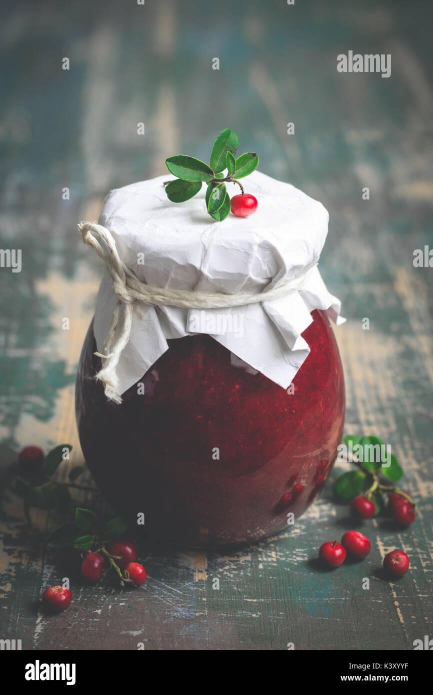 Lingonberry inceppamento nel vaso e frutti di bosco freschi. Messa a fuoco selettiva Immagini Stock