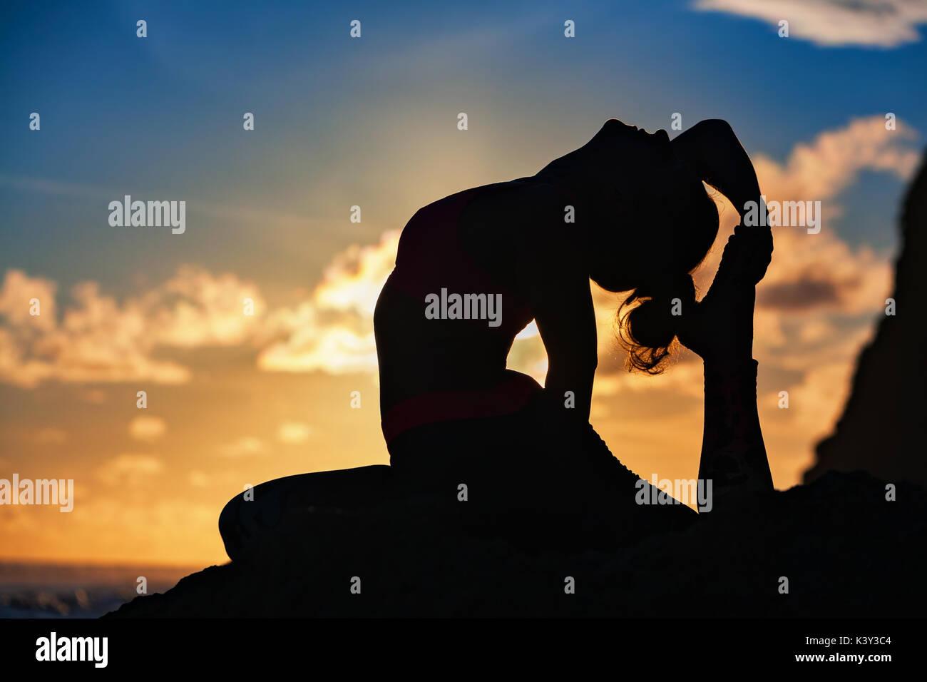 Donna silhouette nera sul Cielo di tramonto sullo sfondo. Giovane ragazza attiva sit in yoga pone sulla roccia spiaggia, stretching per mantenersi in forma. Uno stile di vita sano, fitness. Immagini Stock