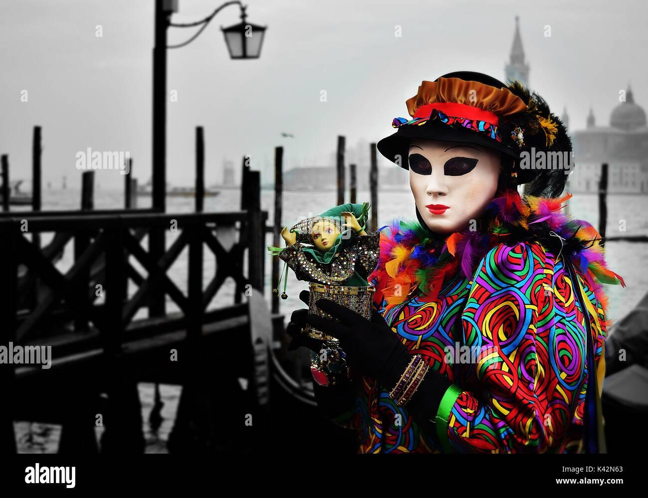 Una persona in un costume pieno di colori luminosi che tiene una piccola bambola al Carnevale di Venezia Immagini Stock
